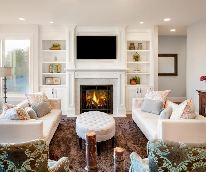 Beautiful living room with, fireplace and lit fire, couches and chairs in new luxury home